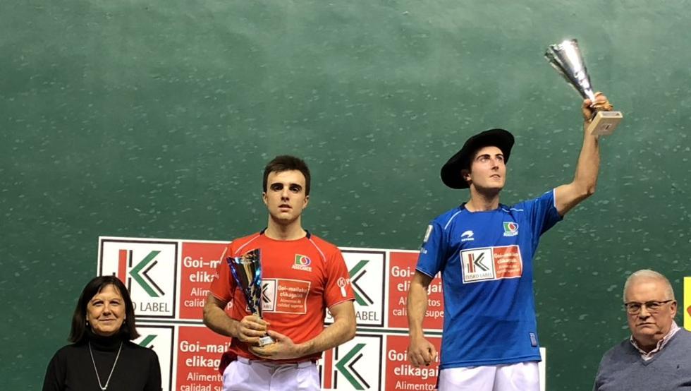 Bakaikoa levanta el trofeo con su txapela de campeón junto a un cariacontecido Peña