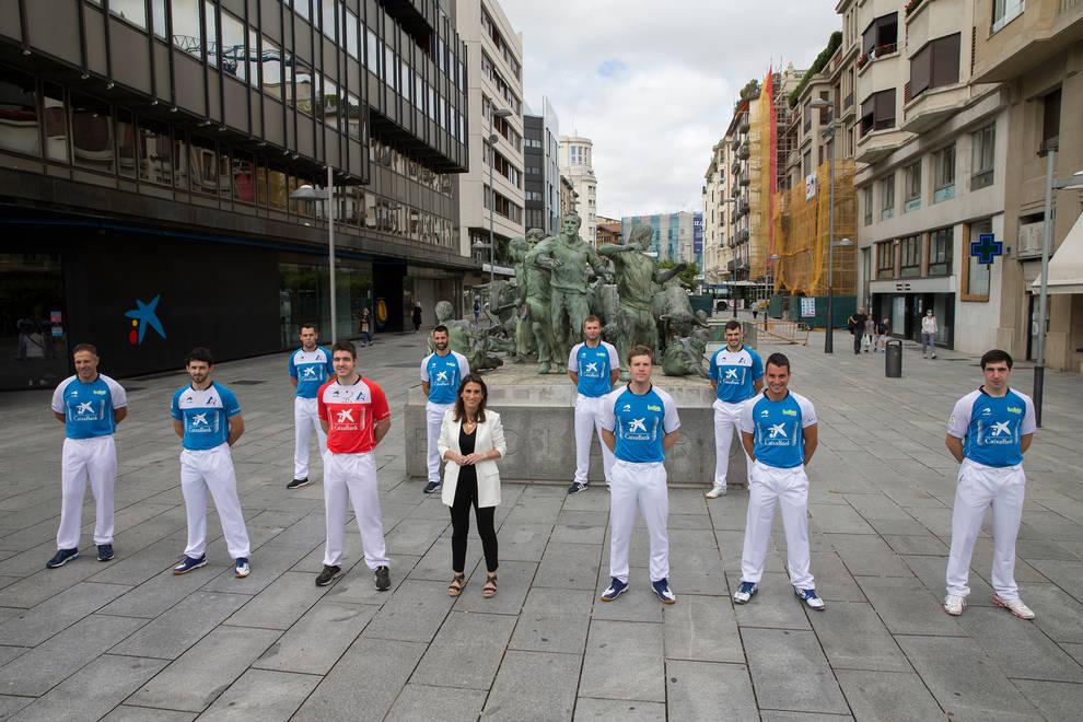 Diez de los participantes en el torneo Masters e Isabel Moreno, directora territorial de CaixaBank, posan delante del monumento al Encierro.