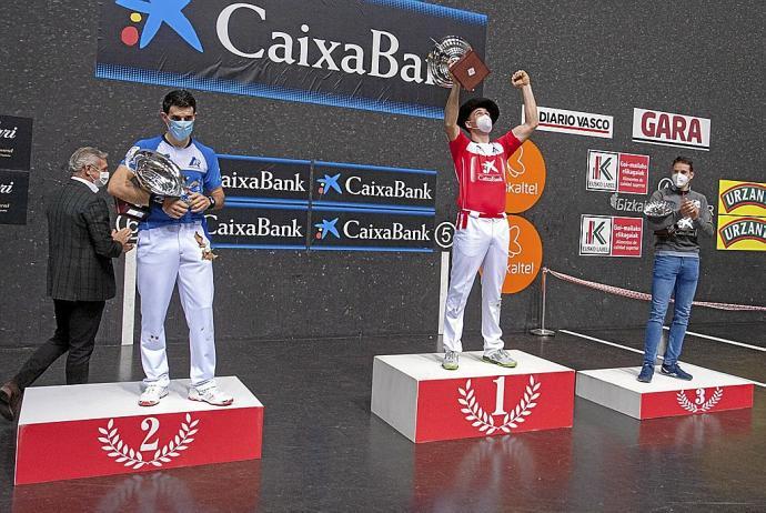 Erik Jaka, con la txapela que le acredita como ganador del Manomanista, celebra la victoria en el podio junto a Jokin Altuna, subcampeón, y Darío Gómez, tercero
