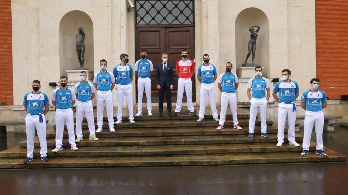 Los doce pelotaris participantes en el Manomanista y Juan Pedro Badiola, director territorial norte de CaixaBank, posan ante el Museo de Bellas Artes
